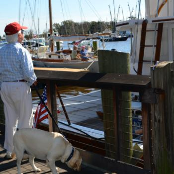 OLder gentleman with dog at a marina