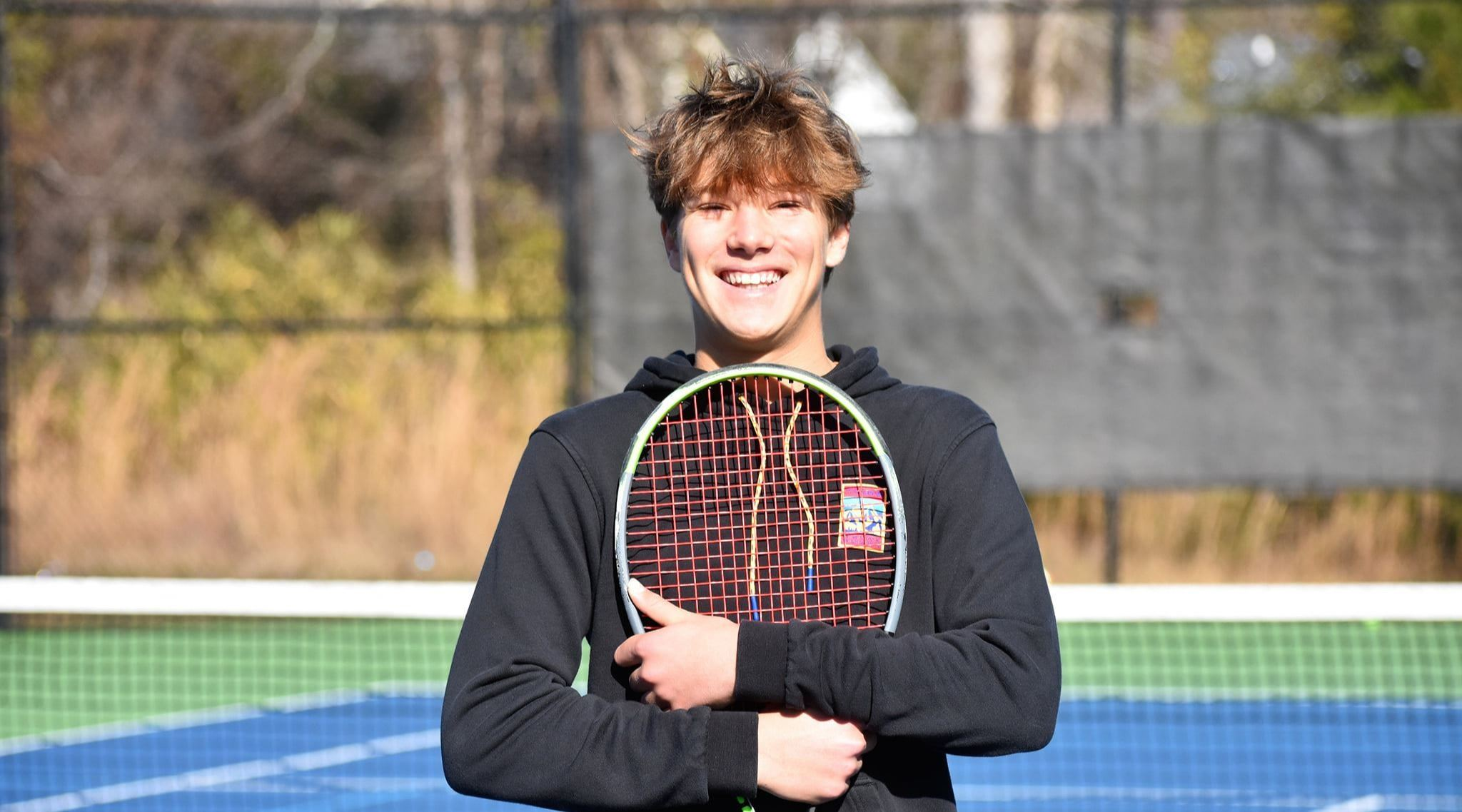 A teenage boy in a black hoodie holds a tennis racquet against his chest