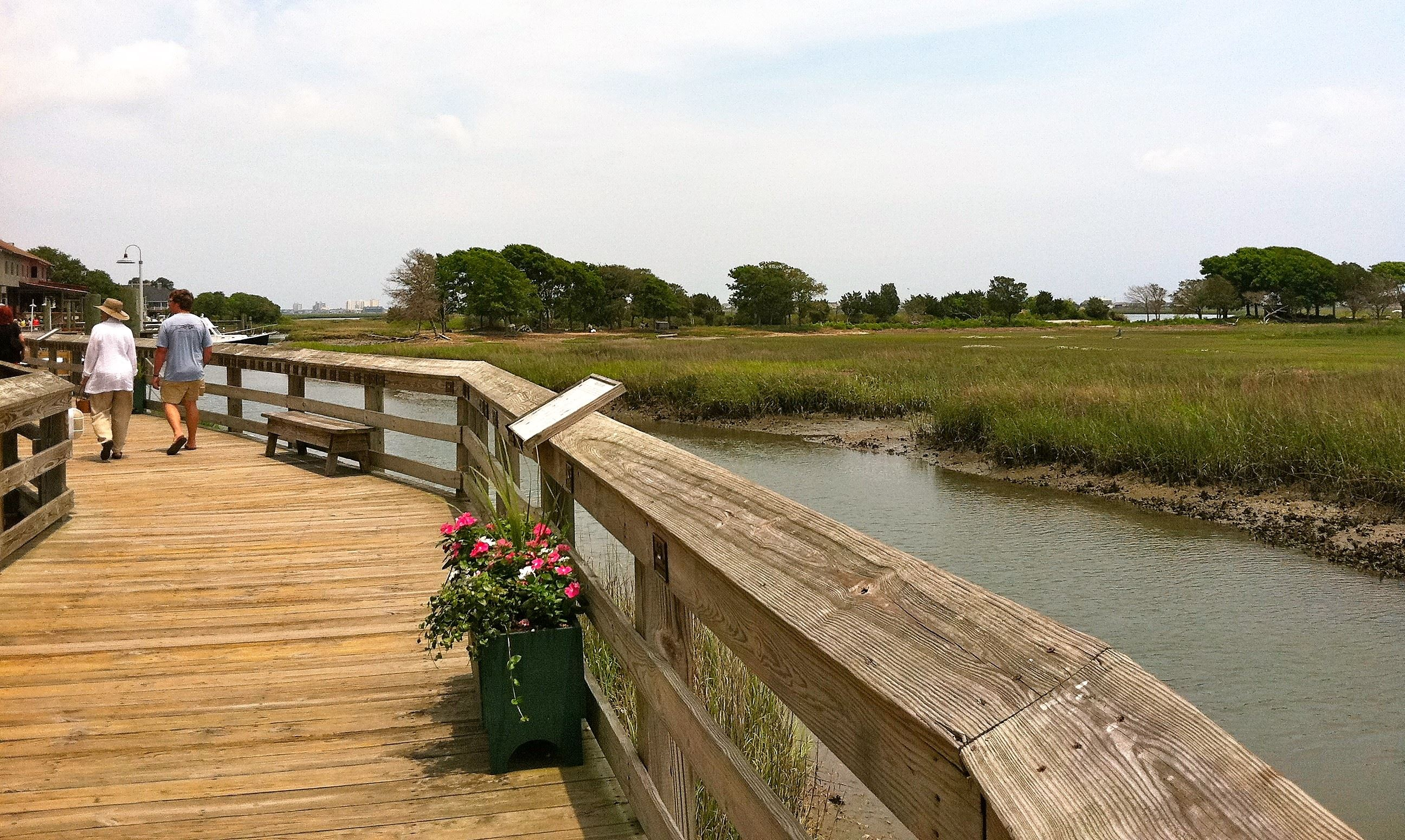 People walk along the wooden boardwalk known as the Murrells Inlet MarshWalk